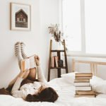 young-woman-lying-bed-with-book (1)